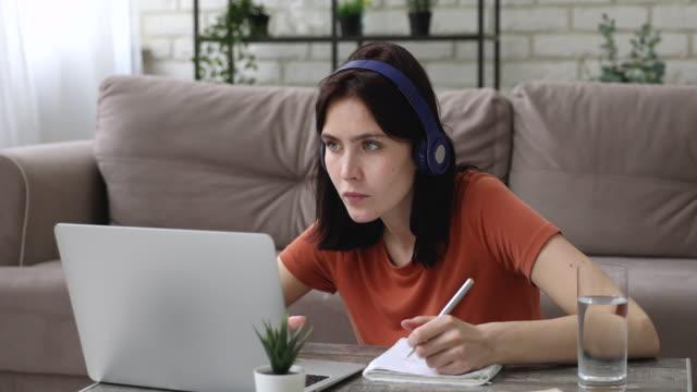 女孩寫在複印本上聽音訊通過耳機衝浪互聯網。 - 文憑 個影片檔及 b 捲影像