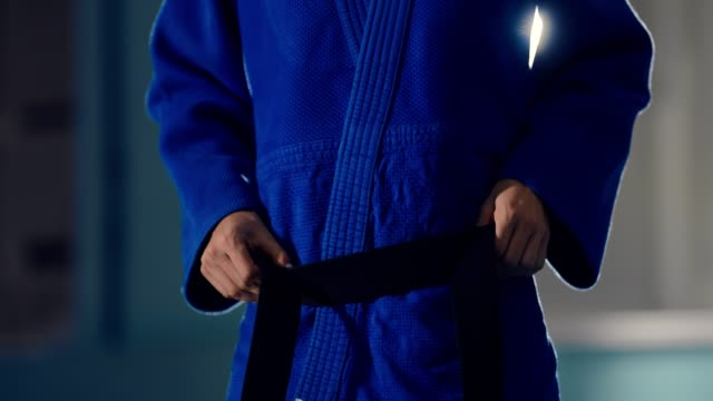 Girl-athlete is tying a black belt in a knot, preparing for training. Close-up.