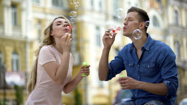 Girlfriend and boyfriend making soap bubbles and kissing, sweet relationship video
