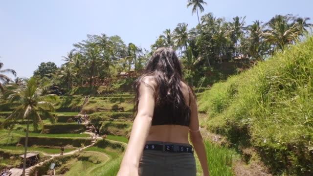 girlfriend pulling boyfriend by hand to explore rice plantations in tegalalang near bali - para heteroseksualna filmów i materiałów b-roll