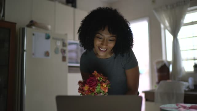 Girlfriend receiving flowers / present of her boyfriend and talking to him on internet via laptop at home