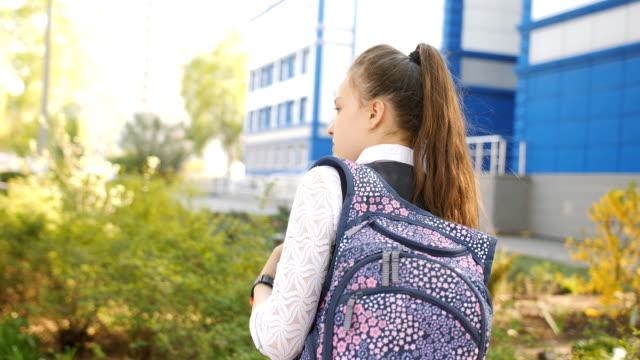 vídeos y material grabado en eventos de stock de novia schoolgirls con mochilas en la luz del atardecer regresando a casa de la escuela, la vista desde la parte trasera. - regreso a clases