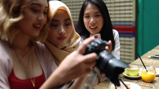 Girlfriends checking out pictures they took Multi-ethnic group of women having fun in the cafe, Kuala Lumpur, Malaysia girlfriend stock videos & royalty-free footage