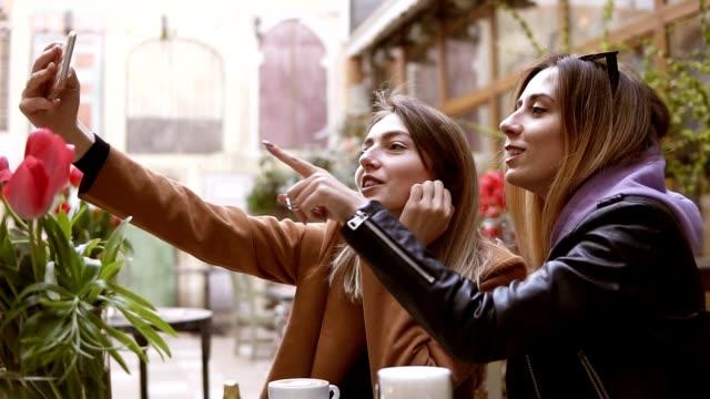 Freundinnen machen Selfie auf Handy-Kamera, während sie in einem Café sitzen. Zwei attraktive Mädchen fotografieren auf der Kamera des Smartphones und täuschen herum, auf den Bildschirm zeigend – Video
