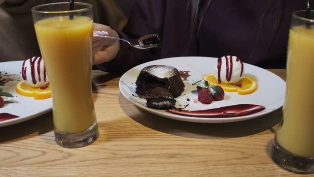 Girlfriends Eating Sweet Dessert in a Restaurant. Chocolate Fondant