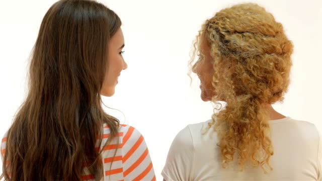 Girlfriends embracing and smiling while standing half-turned video