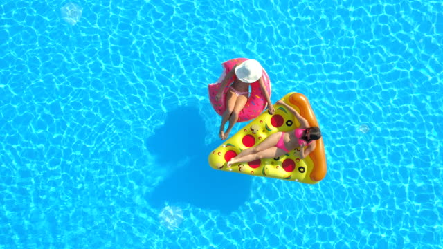 AERIAL Girlfriends enjoying on fun inflatable pizza and doughnut floats in pool AERIAL TOP DOWN Relaxed girls in pink bikini swimsuits laying on fun inflatable pizza and flamingo floating on water. Girlfriends on summer vacation enjoying on pink flamingo and pizza floats in pool swimwear stock videos & royalty-free footage