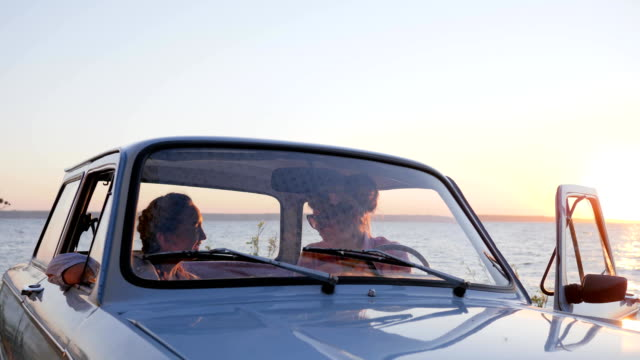 girlfriends in automobile speaks and Point hand to skyline of sea, Friends in salon machine to Embankment near river video