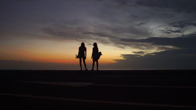 dziewczyny patrzą na piękny widok na zachód słońca po skateboardingu na szczycie góry - łyżwa filmów i materiałów b-roll