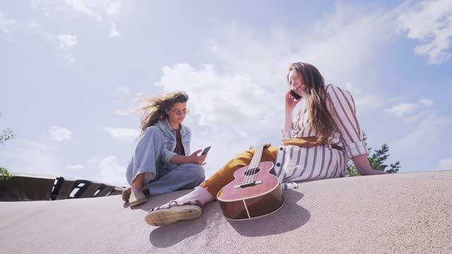 vídeos de stock e filmes b-roll de girlfriends relax in contemporary city park at summer - amizade feminina