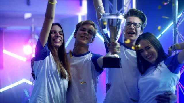 vídeos de stock, filmes e b-roll de meninas e meninos vencedores do esporte / esport / torneio de jogos de vídeo comemorar sua vitória, levantar o troféu. - troféu