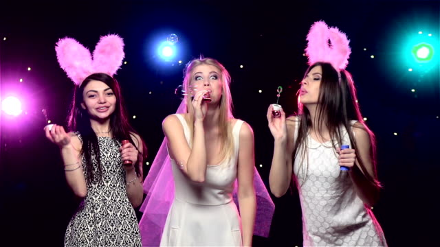 Girls at bachelorette party blowing soap bubbles. Slow motion
