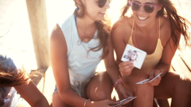 vídeos de stock, filmes e b-roll de meninas na praia olhando fotografias instantâneo de verão - polaroid