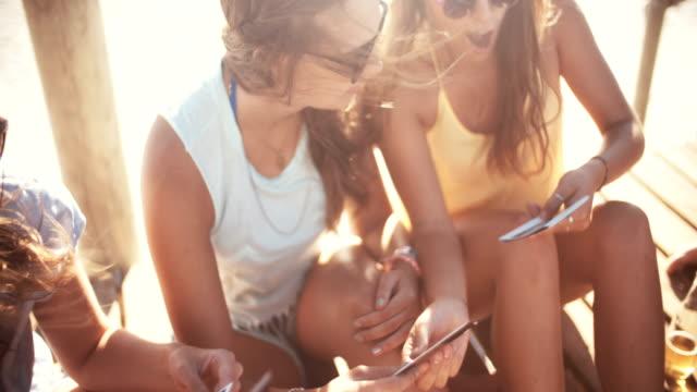 stockvideo's en b-roll-footage met girls at the beach looking photos of their summer - polaroid