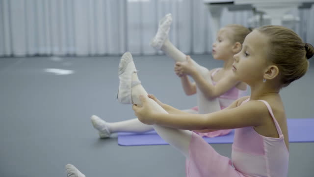 Girls ballerina sit on mat and pull up one leg for stretching muscles video