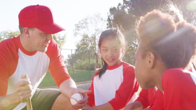 ragazze squadra di baseball e allenatore maschile che parlano di squadra - allenatore video stock e b–roll
