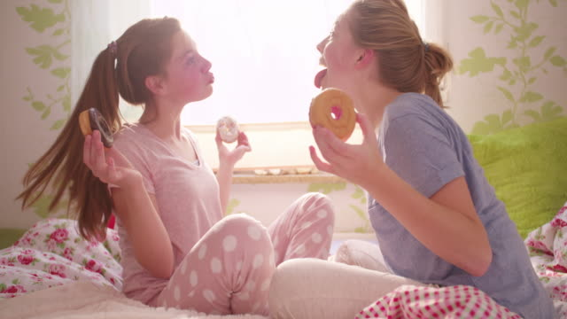 Girls being silly with doughnuts at a pyjama party video