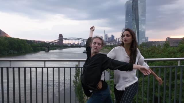 girls dancing side by side on city bridge - fianco a fianco video stock e b–roll