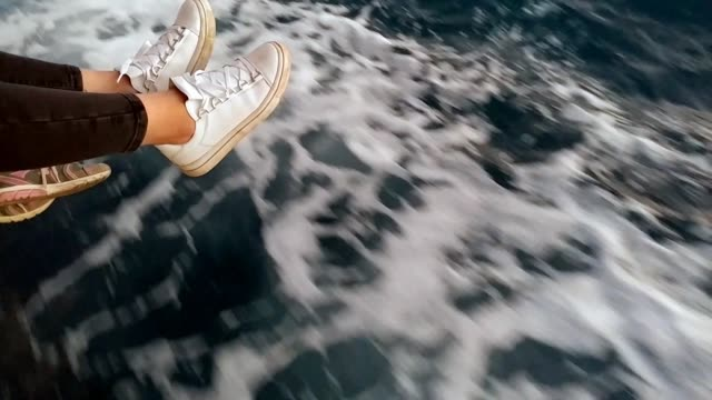 Girls dangling their feet on the boat