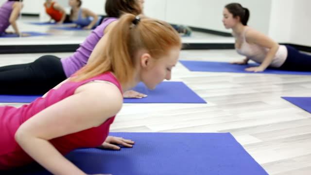 Girls doing exercises cobra position on yoga mats video