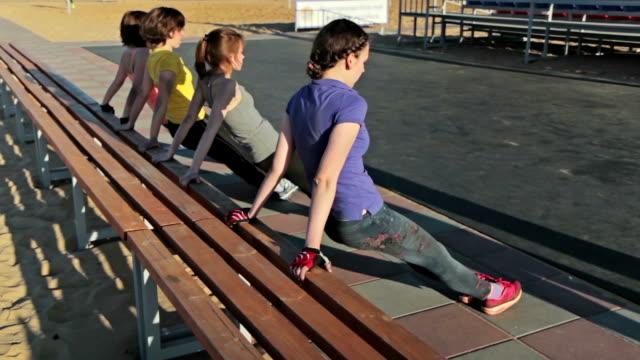 公園のベンチで腕立て伏せをしている女の子 - 人の筋肉点の映像素材/bロール
