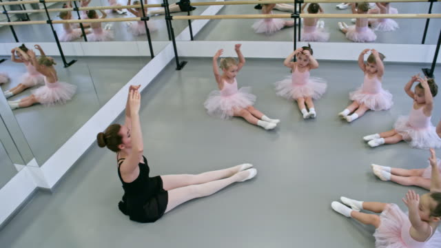 Girls Doing Warm Up Exercises High angle view of group of little ballerinas and their teacher sitting in circle and practicing fifth position when doing warm up exercises for arms dance studio stock videos & royalty-free footage
