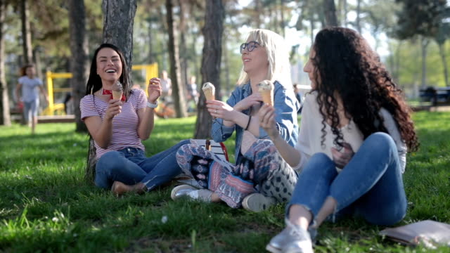 vidéos et rushes de filles profiter de la crème glacée dans le parc - vanille