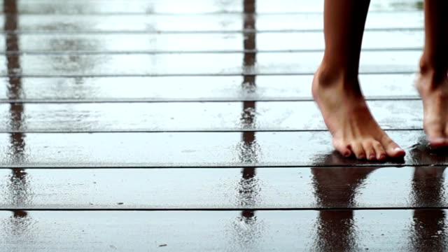 Girl's feet dancing on the wet floor of the porch while raining. video