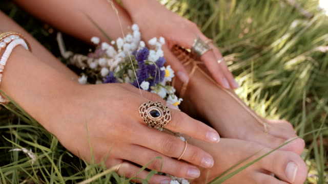 Girl's feet in grass with fresh flowers and gold jewellery Cropped shot of a girl's hands resting on her ankles with her feet resting in lush green grass decorated with wild flowers and gold chain foot jewellery boho stock videos & royalty-free footage