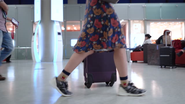 girl's feet walking with luggage in airport. - аэровокзал стоковые видео и кадры b-roll