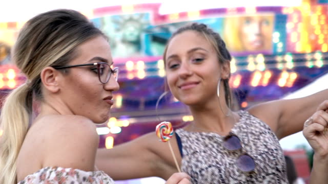 Girls fooling around with lollipops