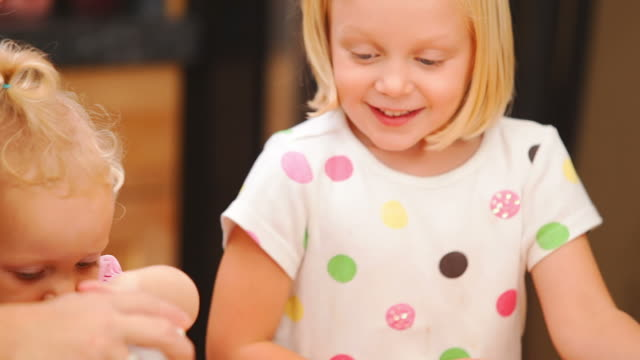 Girls giggle while making cupcakes video
