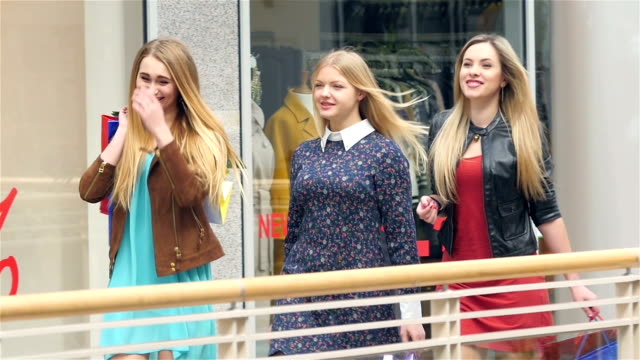 Girls go along and shop talk at the same time, shopping. Close up. Slow motion