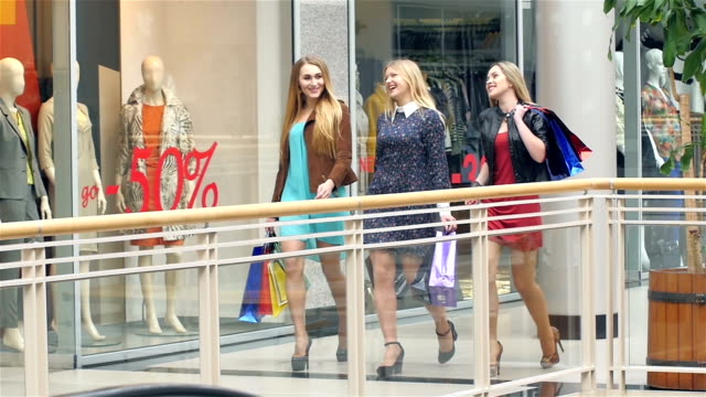 Girls go along and shop talk at the same time, shopping. Slow motion