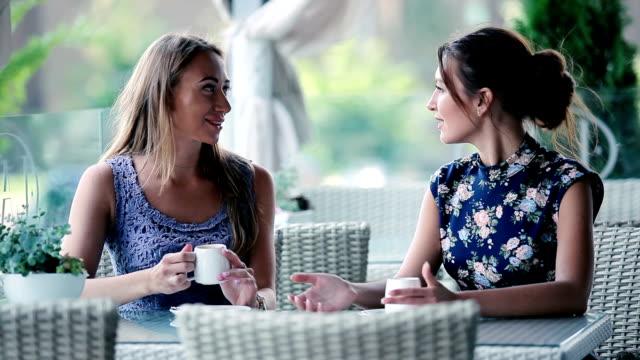 girls gossip while sitting at the terrace. - due oggetti video stock e b–roll