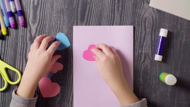 女孩的手粘著一張卡片。情人節 - 手工藝 個影片檔及 b 捲影像