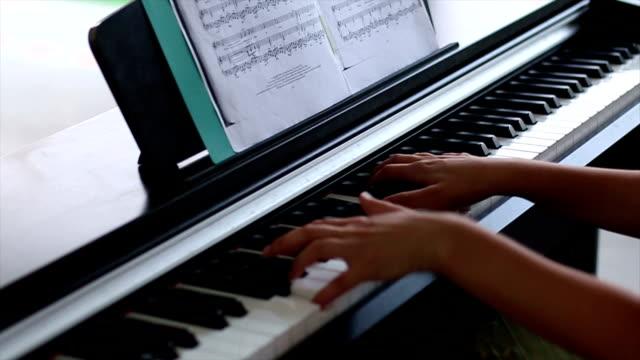 vídeos de stock e filmes b-roll de girl's hands on piano - compositor
