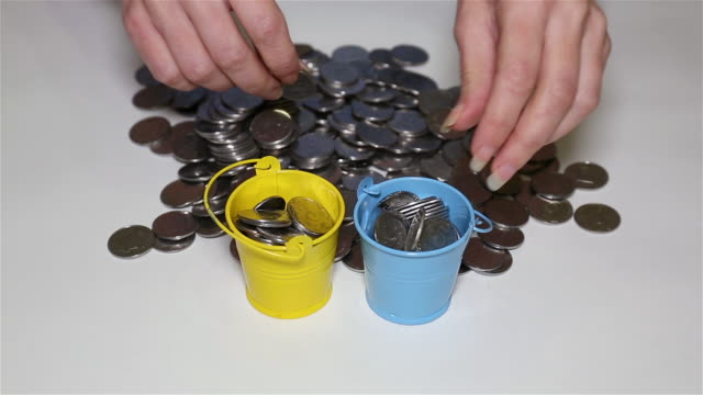 Girl's hands putting coins in small colorful buckets