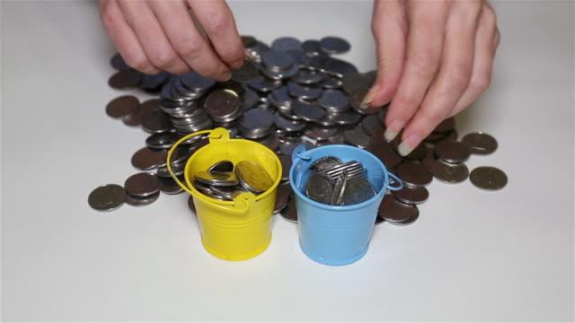 die hände des mädchens stecken münzen in kleine bunte eimer - eimer stock-videos und b-roll-filmmaterial
