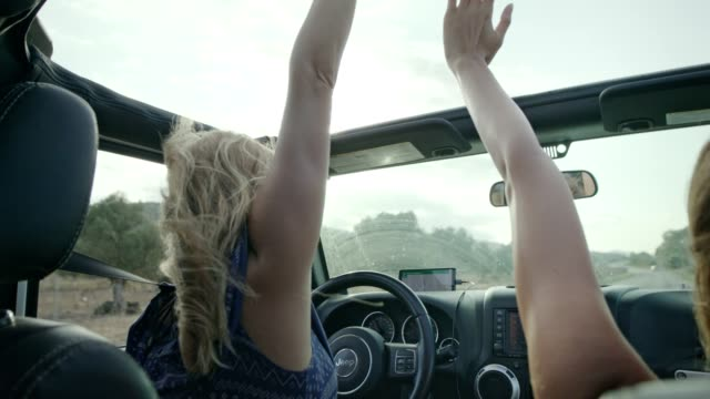 Girls having fun in a SUV. Hands on sun roof.