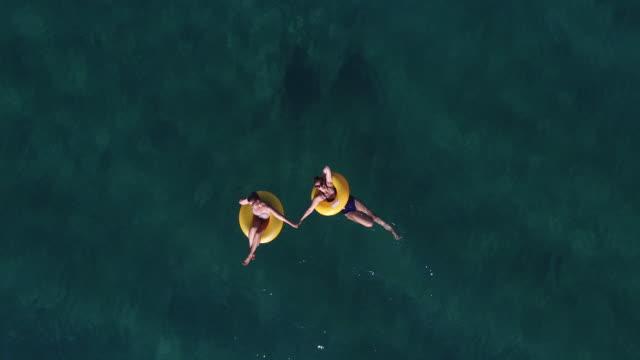 vídeos de stock, filmes e b-roll de garotas se divertindo no oceano 4k - inflável