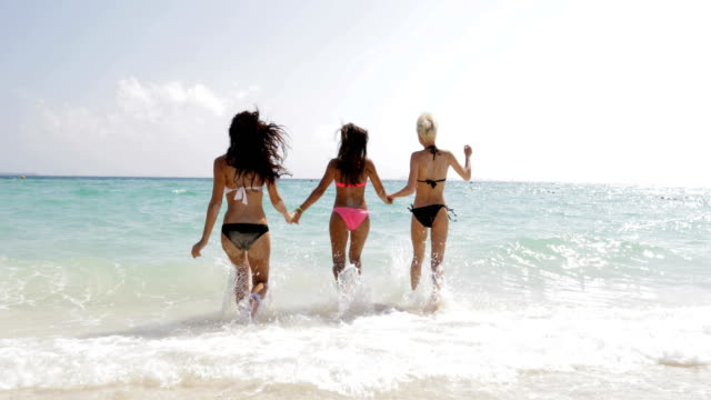 Girls In Bikini Running In Water Holding Hands On Beach Back Rear View, Cheerful Women Group Tourists On Summer Holiday Girls In Bikini Running In Water Holding Hands On Beach Back Rear View, Cheerful Women Group Tourists On Summer Holiday Slow Motion 60 swimwear stock videos & royalty-free footage