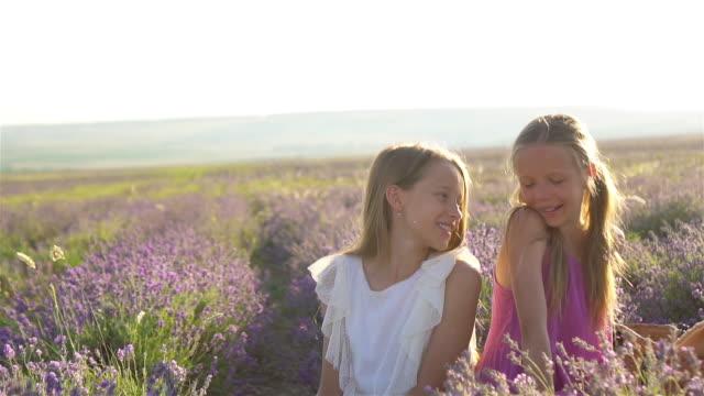 girls in lavender flowers field at sunset in white dress - wschodnio europejski filmów i materiałów b-roll