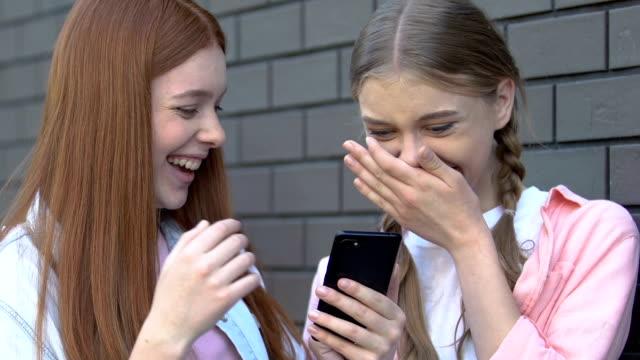 vídeos de stock e filmes b-roll de girls laughing at shameful post with classmate in social media, cyberbullying - ameaça