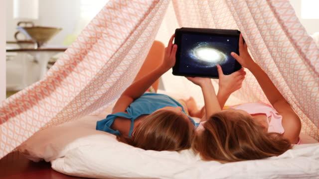 mädchen auf der suche bei digital-tablette. - erforschung des weltalls stock-videos und b-roll-filmmaterial