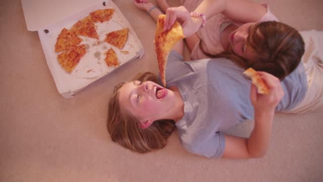frauen liegen auf dem boden in einigen take-away-pizza - teenage friends sharing food stock-videos und b-roll-filmmaterial
