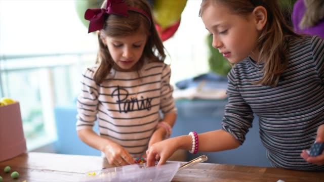vídeos de stock, filmes e b-roll de girls making brigadeiro in a birthday party - brigadeiro