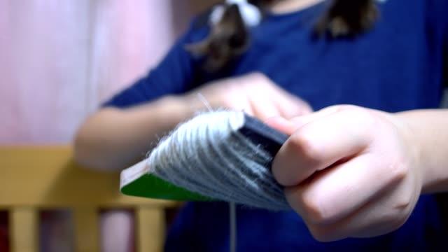 stockvideo's en b-roll-footage met meisjes maken van poppen van strijkers. - touw