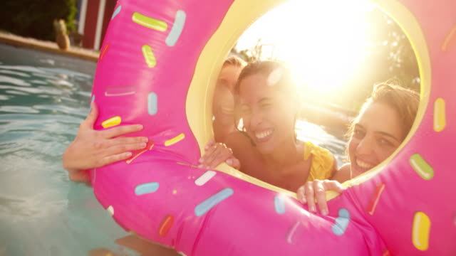 Girls making laughing and having fun in a pool on summer afternoon Three girls floating in a swimming pool with a pool inflatable looking like a big pink donut having fun while laughing on a summer afternoon in a backyard with sunflare pool party stock videos & royalty-free footage