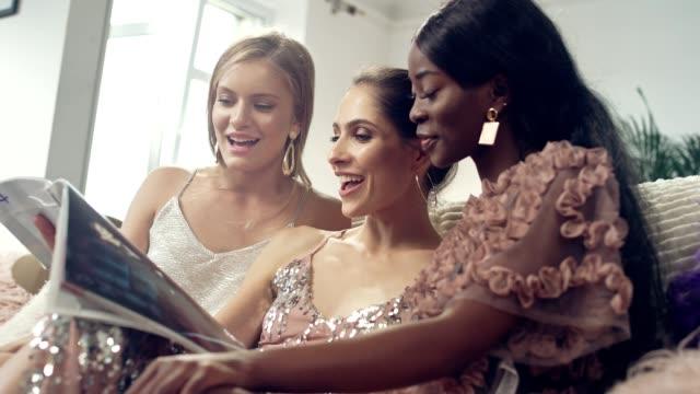 vídeos y material grabado en eventos de stock de diversión nocturna de chicas. revista de lectura de amigos étnicos - feminidad